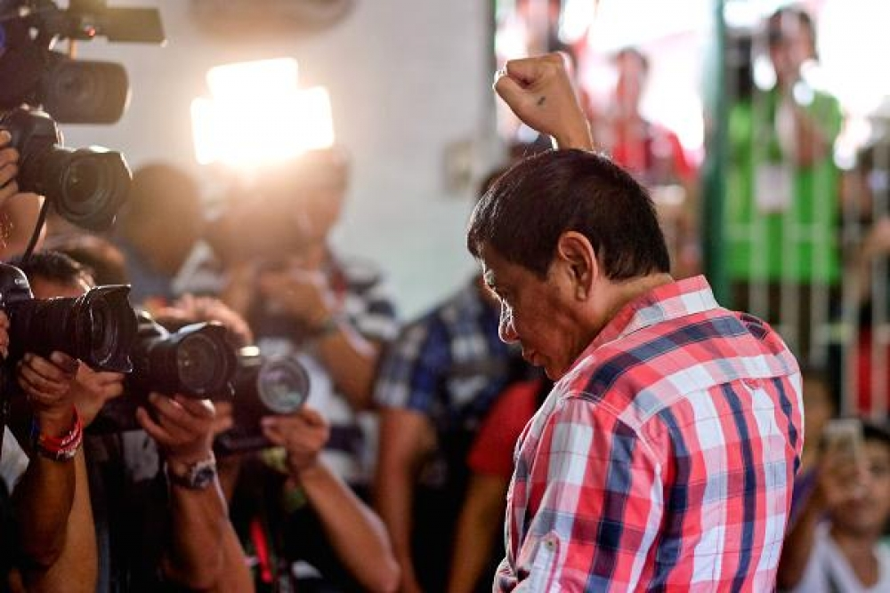 Rodrigo Duterte gestures to members of the media at a polling station in Davao, Mindanao, on May 9.