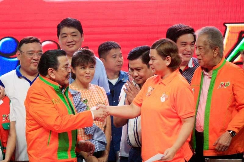 Mayors Joseph Estrada and Sara Duterte shake hands to signify an alliance between their two political parties at the San Andres Sports Complex in Manila yesterday. Looking on are senatorial aspirants (from left) Harry Roque, Imee Marcos, Jinggoy Estrada and the reelectionist Manila mayor's runningmate, Amado Bagatsing. Edd Gumban